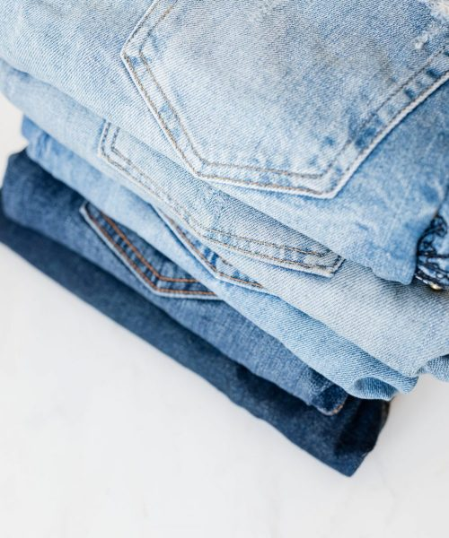 stack-of-jeans-on-white-marble-surface-4210857
