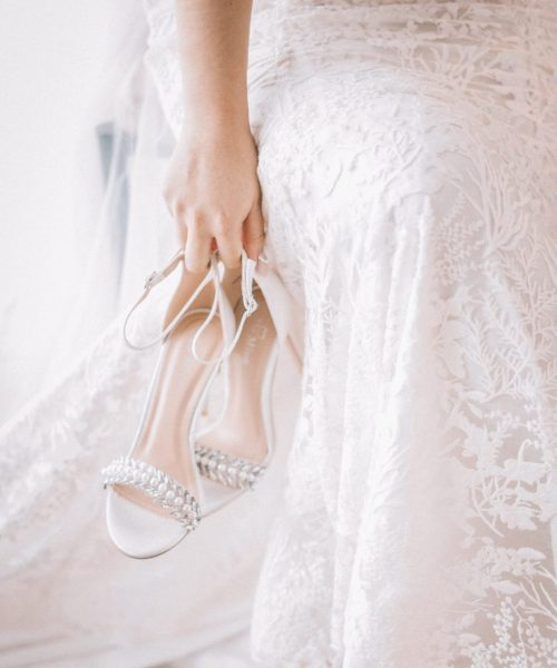 woman-in-white-gown-carrying-white-sandals-2085523
